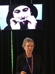 "Atlantic Works Gallery artist Charlene Liska in front of ""Prophecy I Machine Transcription"": video, 2017 (image on screen is Elson, the Bird Caller)"